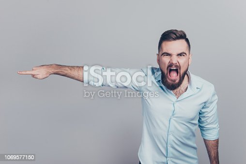 istock Hr corporate ceo concept. Close up studio photo portrait of mad serious furious frustrated manager with opened mouth showing away looking at camera isolated gray background copyspace 1069577150