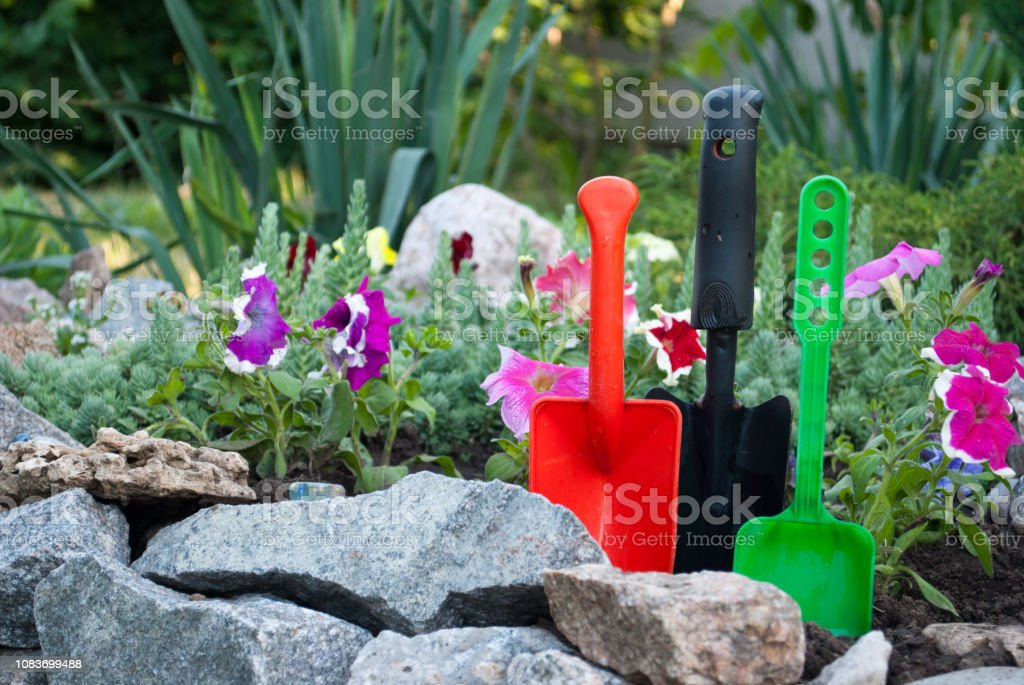Three plastic shovels green black red, on the ground spring works...