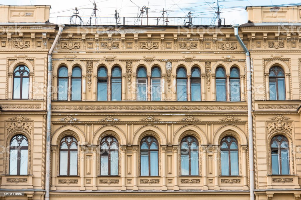 HThe facade of the historic building yellow-orange building with window arches. stock photo