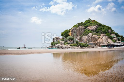The Beach At Hua Hin In Thailand With A Large Golden Standing Buddha Statue In The Background