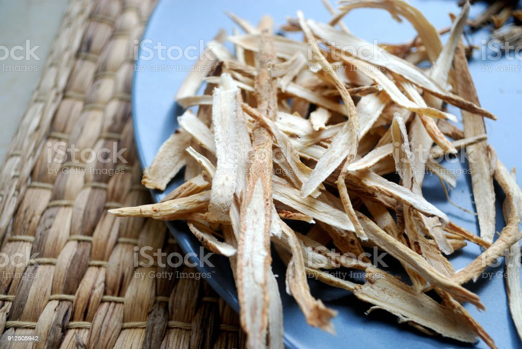 Huang Qi (Astragalus) root sliced and dried on a plate. stock photo