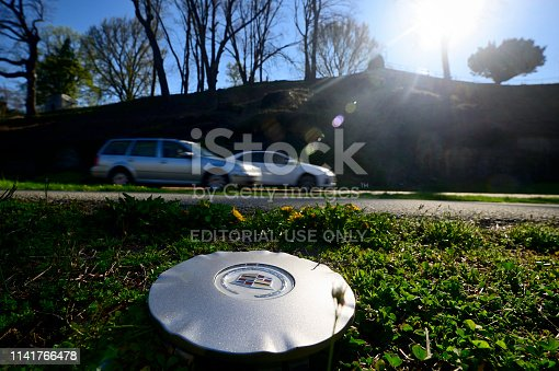 Philadelphia, PA, USA - April 10, 2019; Hubcap cover remains in the grass on the side of the road as traffic rushes past on Kelly drive in Philadelphia, PA.