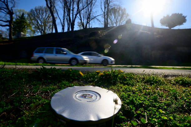 Hubcap left on side of road as traffic rushes past stock photo