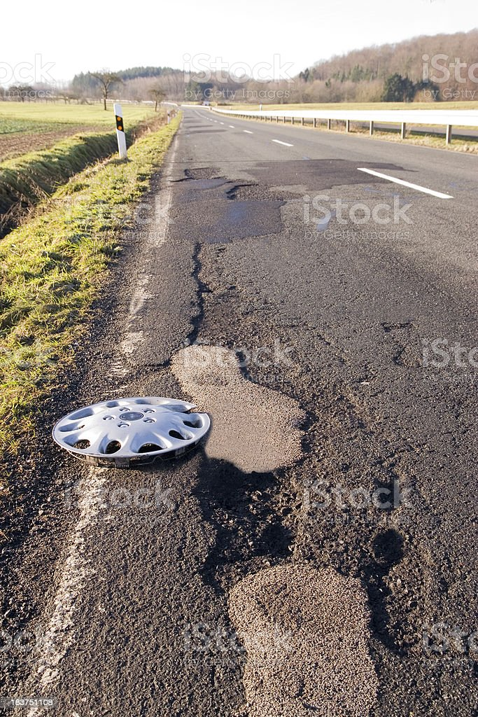 Hubcap on a Damaged Road stock photo