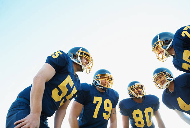 Huddle of Pro American football team against clear sky Low angle view of team of pro footballers in blue uniform discussing their next tackle safety american football player stock pictures, royalty-free photos & images