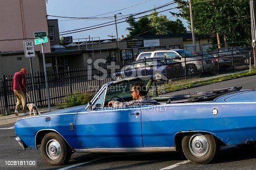 Hudson, New York, USA August 26, 2018 A man drives a convertible on Warren Street, in Hudson, the vintage and antique capital of New York.