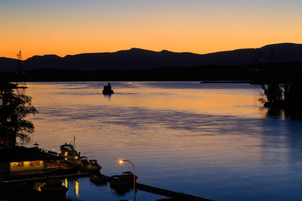 Hudson River at dusk in Hudson with lighthouse and boats stock photo
