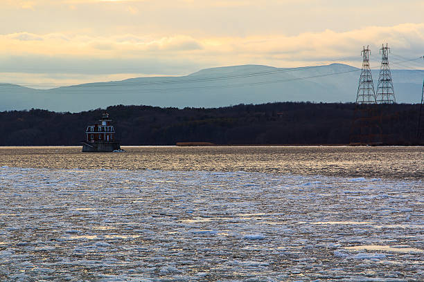Hudson River Athen's Lighthouse with barge in winter stock photo