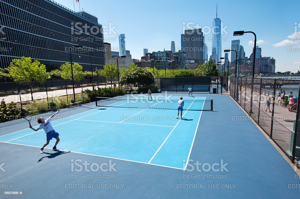 New York City residents playing tennis on the Hudson River Park...