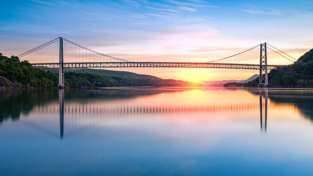 Hudson River Sunrise Bear Mountain Bridge at sunrise (long exposure). Bear Mountain Bridge is a toll suspension bridge in New York State, carrying U.S. Highways 202 and 6 across the Hudson River hudson river stock pictures, royalty-free photos & images