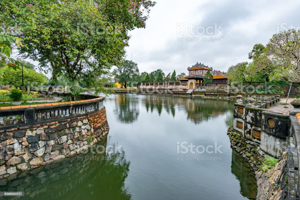 Hue - Vietnam. December 08, 2015. Imperial Enclosure Top choice historic site in Hue, Vietnam. The Imperial Enclosure is a citadel-within-a-citadel, housing the emperor's residence, temples and palaces, and the main buildings of state, within 6m-high, 2.5km-long walls. What's left is only a fraction of the original – the enclosure was badly bombed during the French and American Wars, and only 20 of its 148 buildings survived. This is a fascinating site easily worth half a day, but poor signage can make navigation a bit difficult. Restoration and reconstruction is ongoing. Ancient Stock Photo