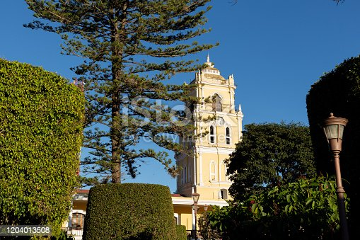Huehuetenango Central Park with clock tower surrounded by trees Latin American peoples