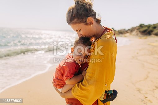 Photo of mother hugging her baby boy while enjoying together at the beach