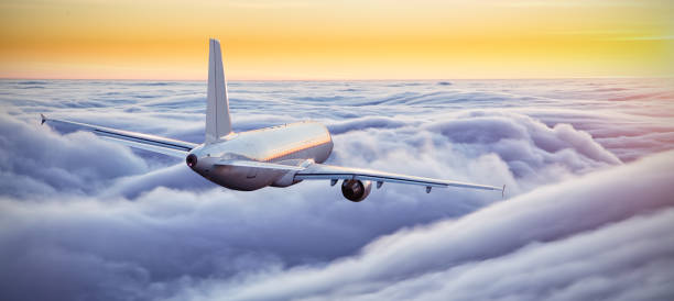 Huge airplane flying above clouds in dramatic sunset stock photo
