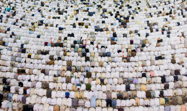 A huge amount of people in one place Thousands of crowded people standing together in circle order lines praying in The Holdy Mosque in Mecca, Saudi Arabia circumambulation stock pictures, royalty-free photos & images