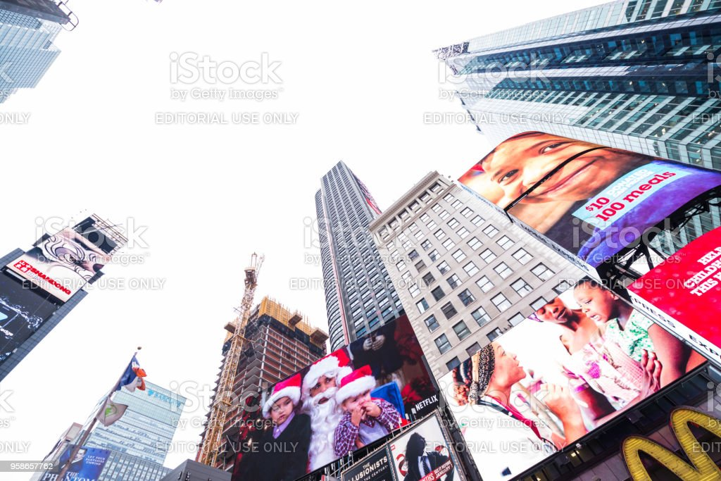 Huge billboards on display in Time Square NYC displaying adds to support hungry kids stock photo