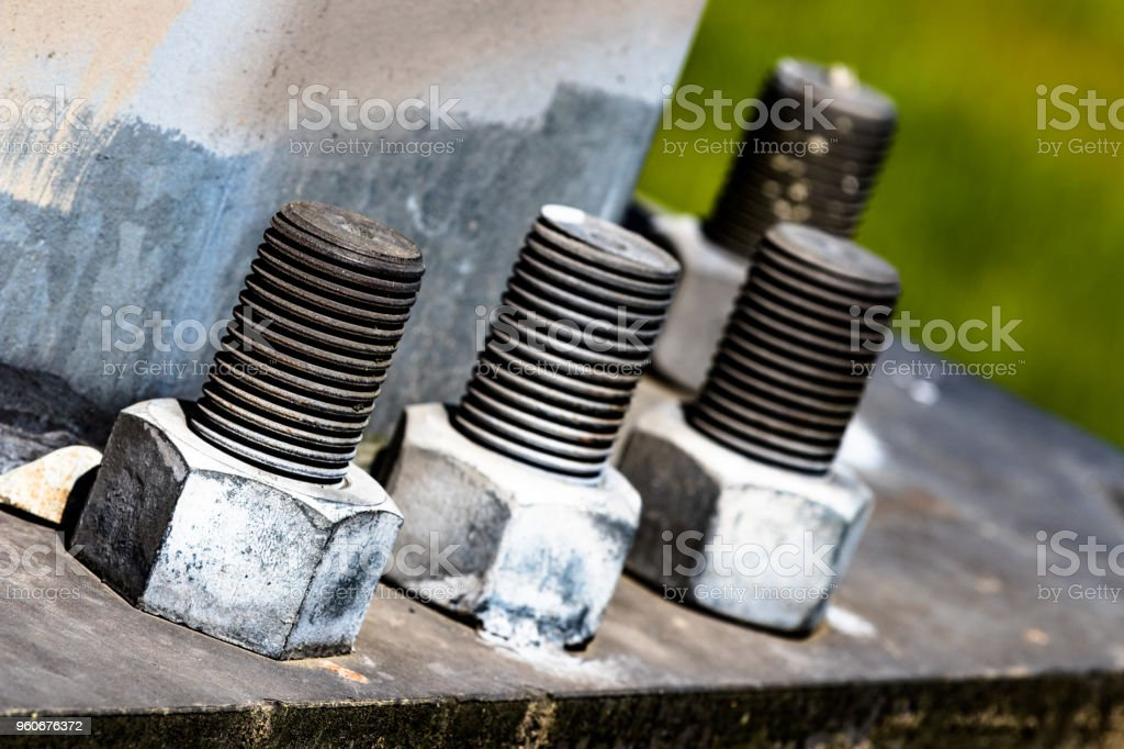 Huge bolts and nuts together in a flange fastening a giant pole in the air stock photo