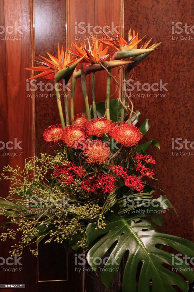 Huge bouquet with Strelitzia flowers in a vase standing on the floor...