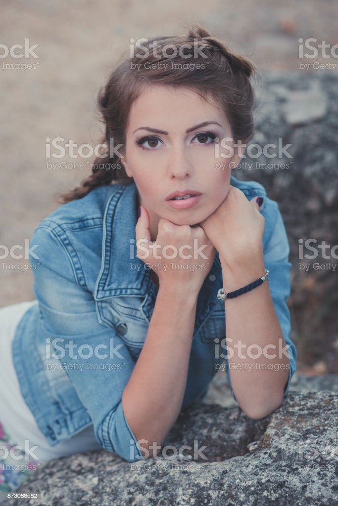 Huge brown eyes young lady woman posing in central park on stone wearing blue jeans jacket white shirt.Brunette beauty with pigtail and brackets on shining white teeth stock photo
