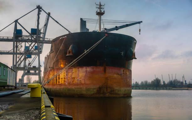 huge bulk carrier in a seaport at sunrise