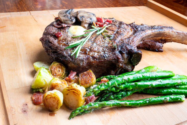 Huge Cowboy Cut Rib Eye Beef Steak with Ketogenic Vegetables on a Plate stock photo