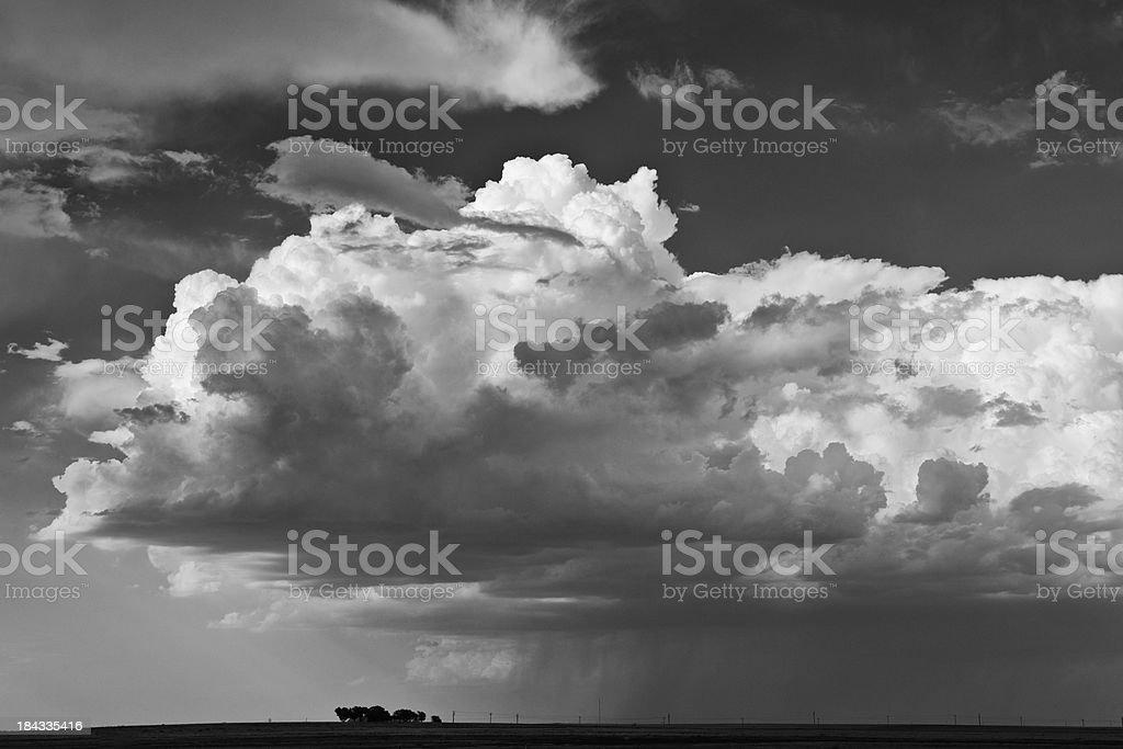 Huge, dark storm clouds threaten small farm below royalty-free stock photo