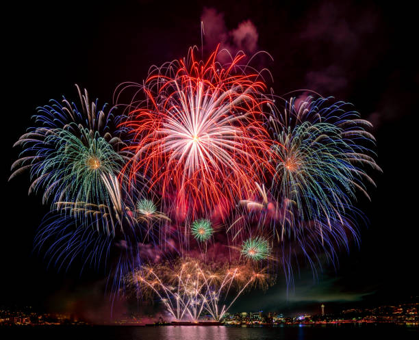 Huge Epic fireworks over lake water display for holiday celebration with Seattle skyline in background stock photo