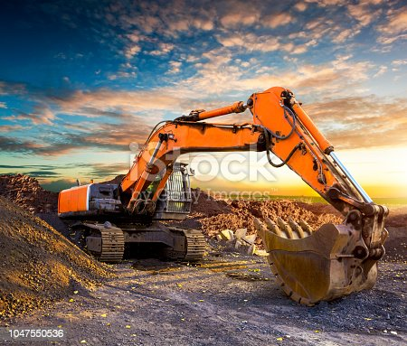 Excavator at a construction site against the setting sun. Excavator on the background of the setting sun. Huge excavator in the evening. Old excavator on a construction site.