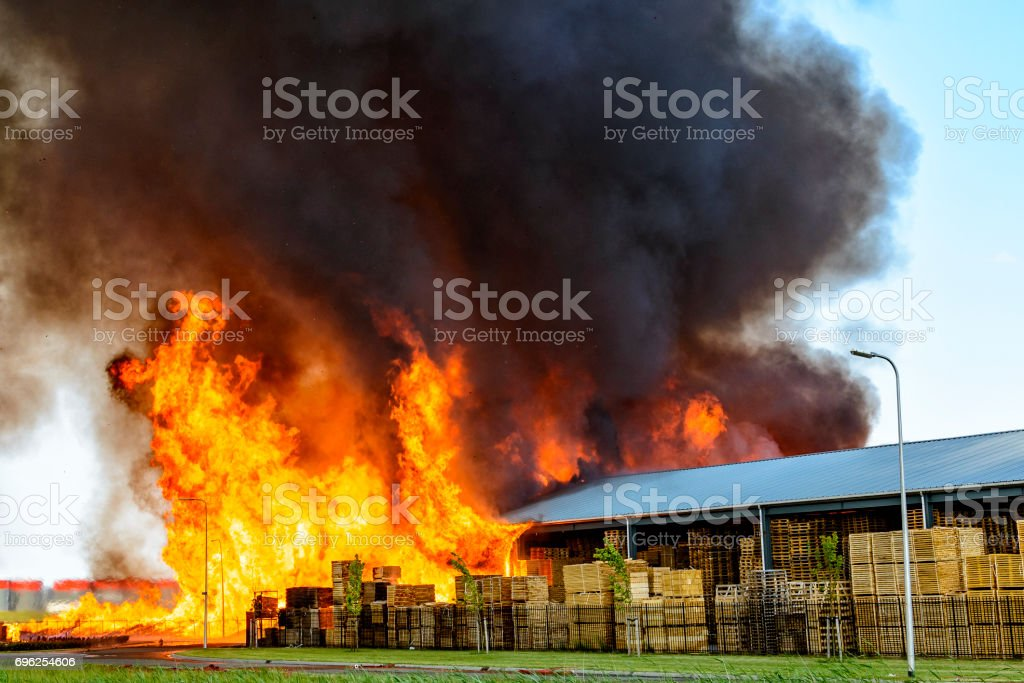 Huge flames from a factory on fire in industrial area stock photo