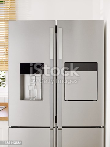 Front view of gray fridge in domestic kitchen