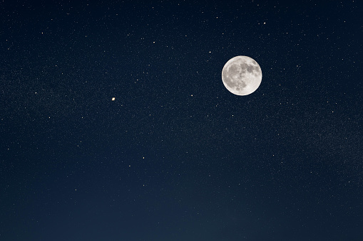 Huge full moon on the night sky with bright stars