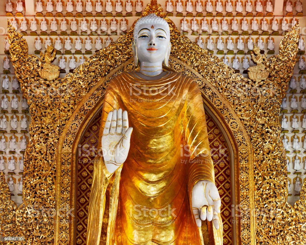 Huge gold statue of standing Buddha in buddhist temple stock photo