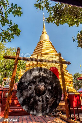 A huge gong  hangs in front of a stupa in a temple in Chang Mai