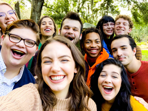 Huge group of cute spunky fun millenial age young adults in a selfie style mobile phone photo acting silly stock photo