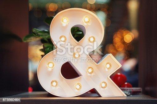 istock A huge illuminated ampersand on the table 873560464