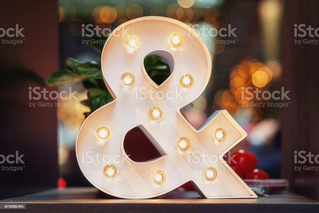 A huge illuminated ampersand on the table stock photo