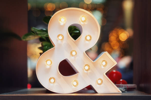 a huge illuminated ampersand on the table - ampersand stock pictures, royalty-free photos & images