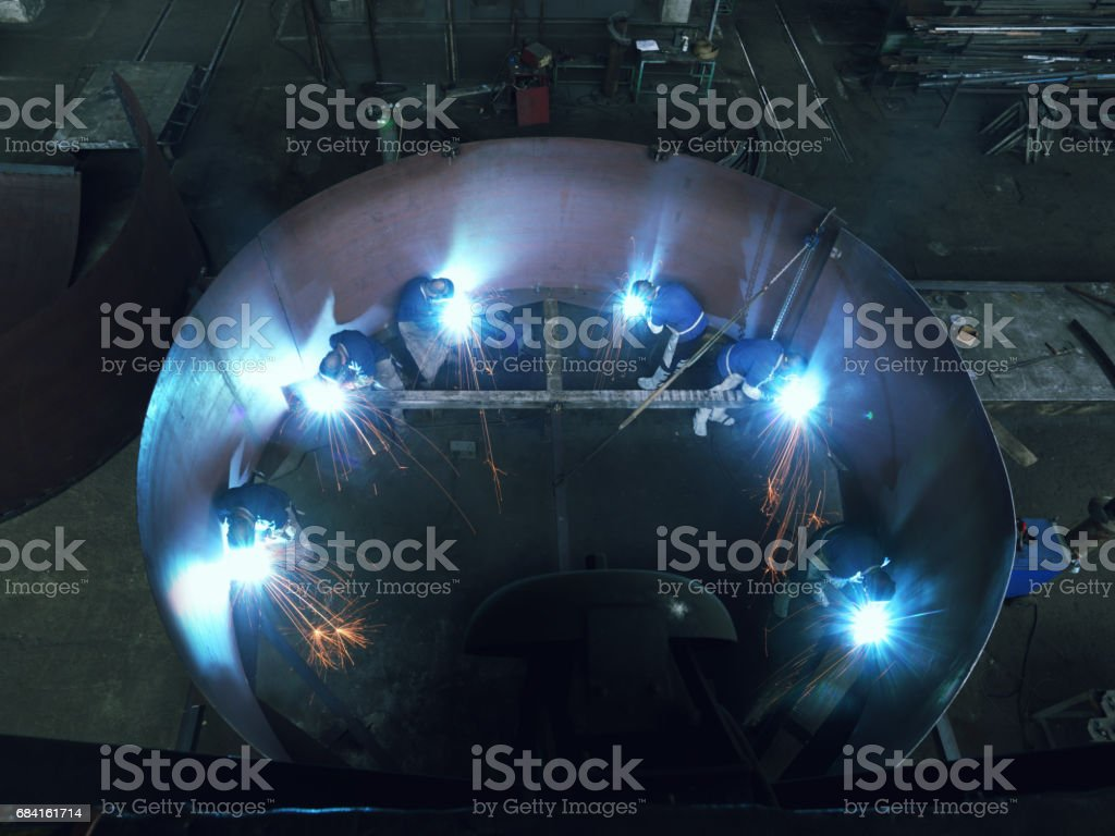 Welding inside of huge metal cylinder, two welders, multiple...