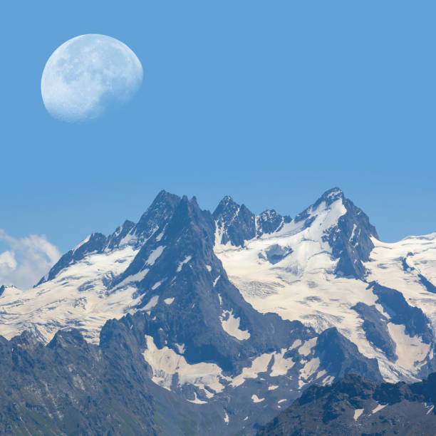 huge moon above a snowbound rock huge moon above a snowbound rock land feature stock pictures, royalty-free photos & images