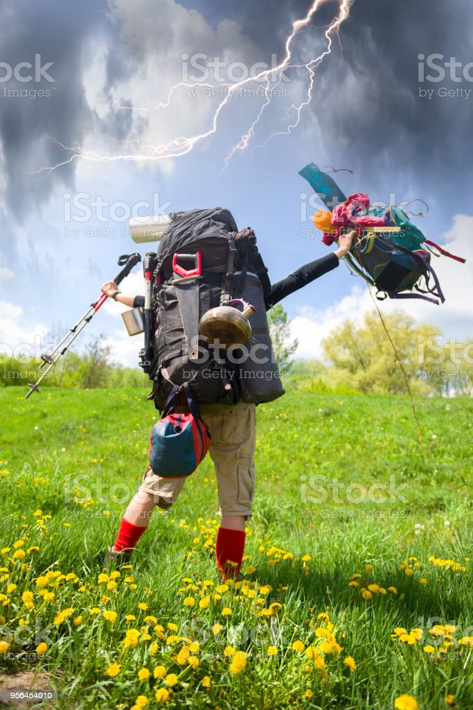 huge novice backpack in the mountains stock photo