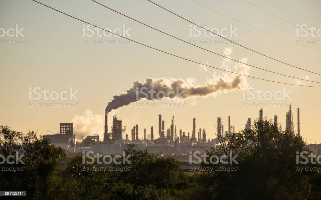 Huge Oil Refinery with Large Smoke Stack and Climate Change Amber Colors stock photo