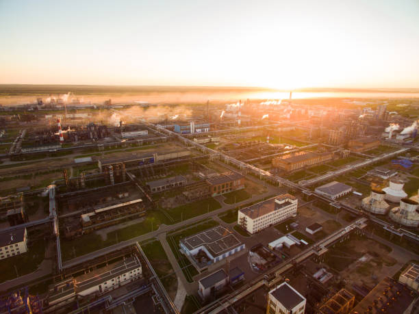 A huge oil refinery with metal structures, pipes and distillation of the complex at sunset. Aerial view stock photo