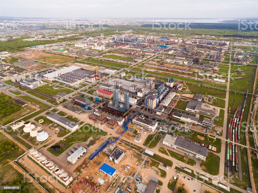 A huge oil refinery with pipes and distillation of the complex on a green field surrounded by forest. Aerial view stock photo