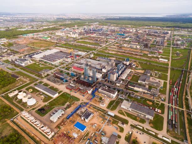 een enorme olieraffinaderij met pijpen en distillatie van het complex op een groen gebied, omgeven door bos. luchtfoto - industriegebied stockfoto's en -beelden