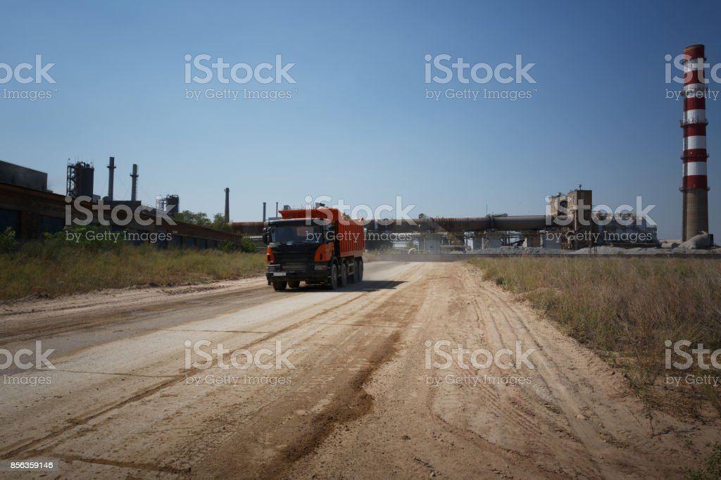 A huge orange tip truck with a shadow driving on a road on a natural background. Huge transporter in a sandy quarry. stock photo