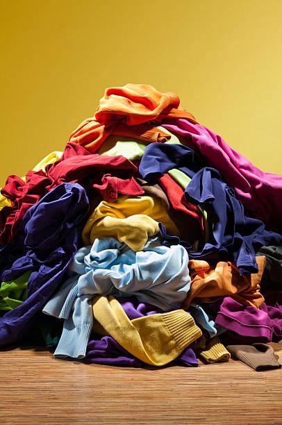 huge pile heap of dirty clothes on golden background - giyim eşyası stok fotoğraflar ve resimler