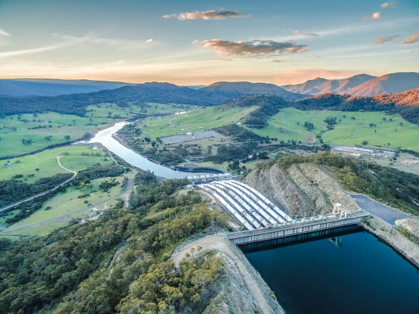 huge pipes of tumut hydroelectric power station at sunset - diga foto e immagini stock