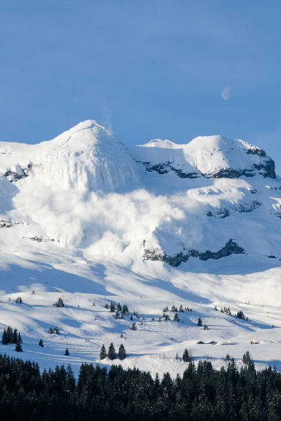 Huge real avalanche in the French Alps with the moon and blue sky stock photo