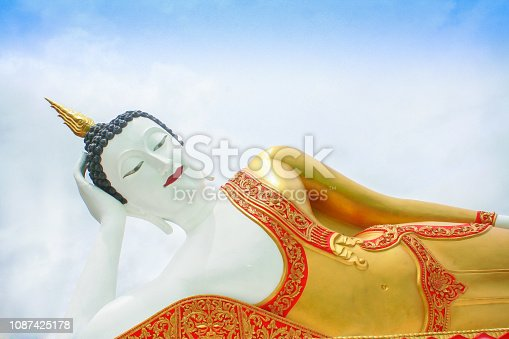 Huge reclining buddha image on blue sky with cloudy at Doi Kham temple in Chiang Mai of Thailand
