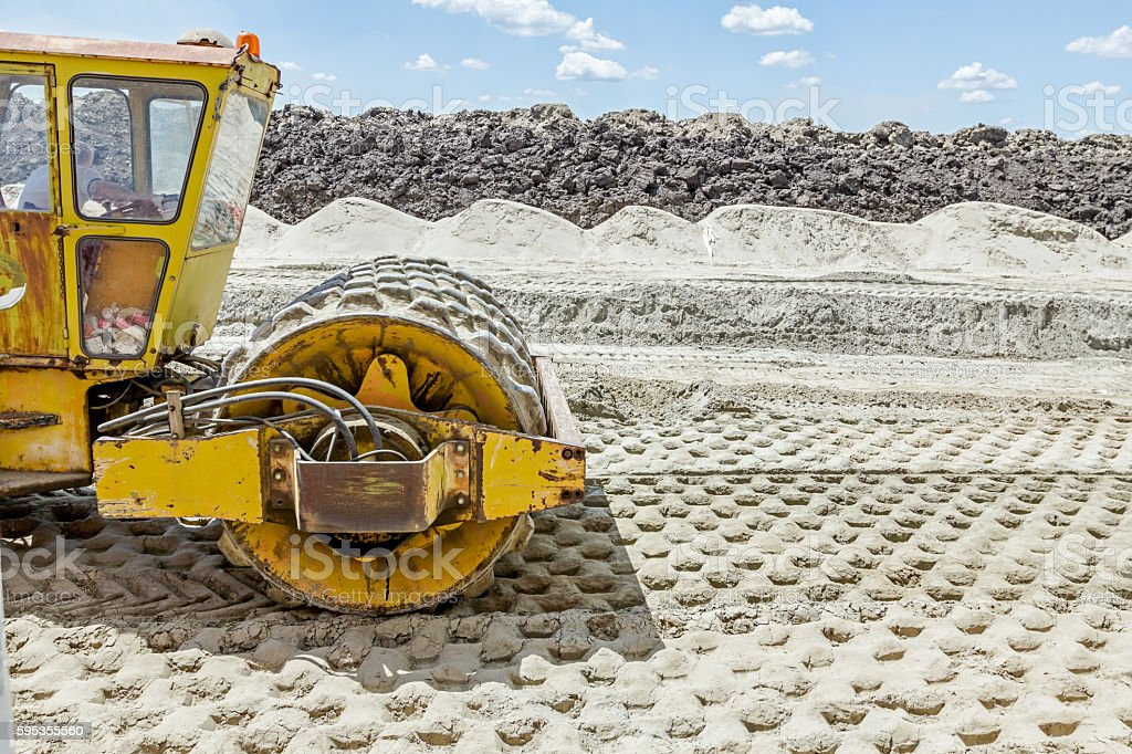 Huge road roller with spikes is compacting soil at construction stock photo